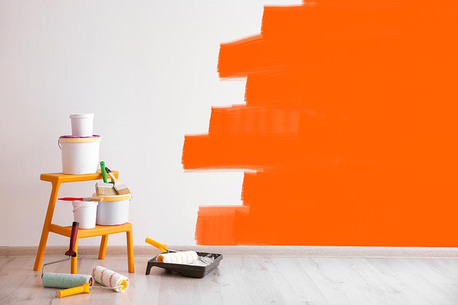 Botes de pintura, escalera y una pared naranja a medio pintar de fondo